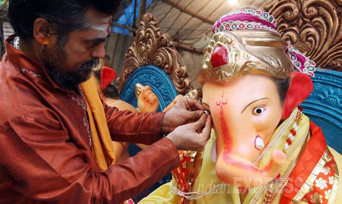 A priest is seen giving last minute touch up to the eye of a Ganpati idol in Vadodara. (Source: Express Photo By Bhupendra Rana)