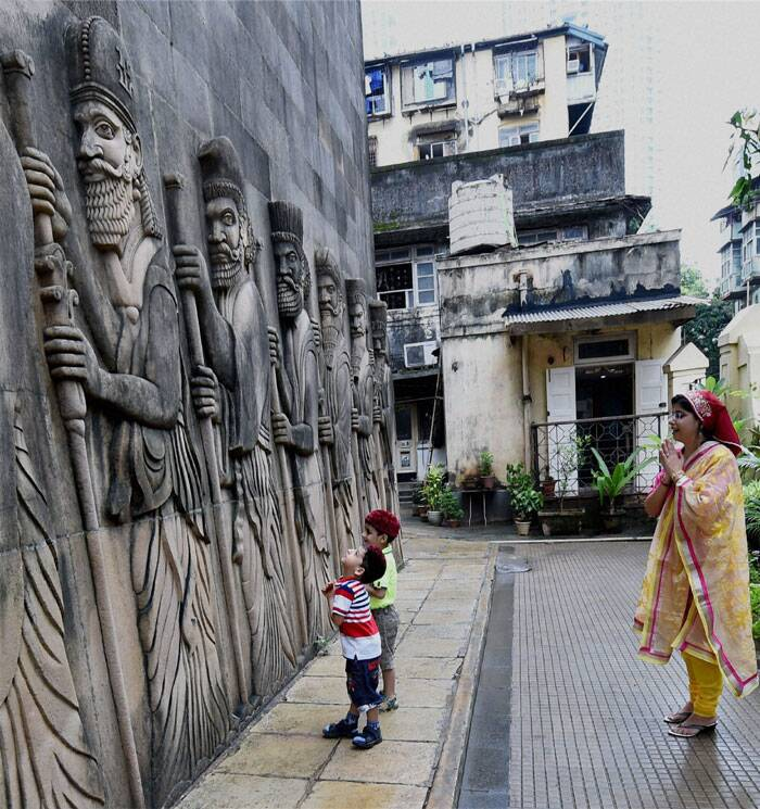 A Parsi woman along with her kids prays outside a fire temple on the occasion of Parsi New Year in Mumbai on Monday. (Source: PTI)