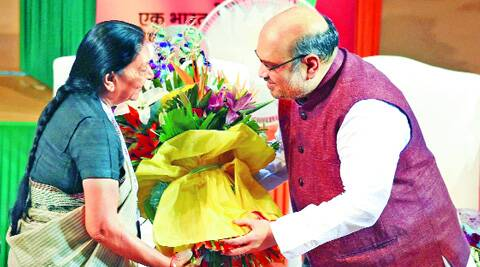 Chief Minister Anandi Patel greets Amit Shah after he was formally announced as BJP chief at the party's National Council meet in New Delhi on Saturday. PTI