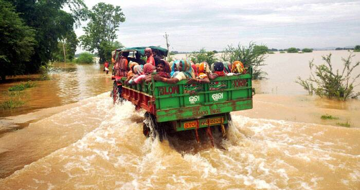 People shift by a tractor from a flooded village in Khurda district of Odisha on Tuesday. (Source: PTI)