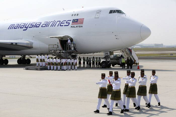 The remains of victims of the MH17 disaster are carried from a plane during a repatriation ceremony at the Bunga Raya complex of KLIA airport in Sepang. (Source: Reuters)