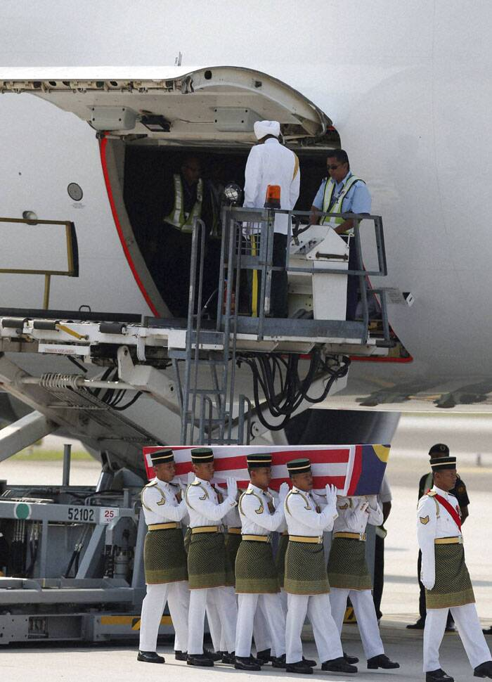 Malaysian Army soldiers carry a coffin containing one of the bodies of the downed MH17 flight upon arrival at Kuala Lumpur International Airport in Sepang, Malaysia. <br /> The bodies and ashes of 20 Malaysians killed when Malaysian Airlines Flight 17 was shot down over Ukraine in July have arrived in Kuala Lumpur, the first repatriation of victims from the flight to the country.(Source: AP)