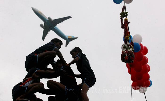 Young boys climbs up the human pyramid as an airplane passes over them. (Source: Express photo by Prashant Nadkar)