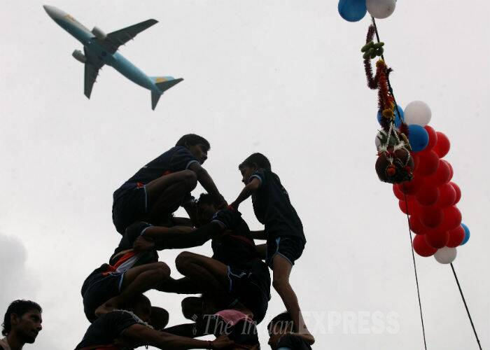 People of Mumbai celebrate Dahi Handi near Santacruz airport as a plane can be seen taking off. (Source: Express photo by Prashant Nadkar)