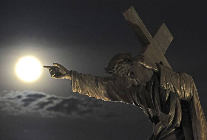 A supermoon rises above a Jesus Christ statue in front of the Holy Cross church  in Warsaw, Poland. (Source: AP)