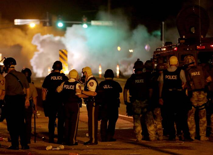 Police wait to advance after tear gas was used to disperse a crowd during a protest for Michael Brown, who was killed by a police officer. (Source: AP)