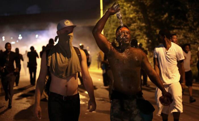 Protestors retreat from tear gas after marching toward police in Ferguson, Mo. on Sunday. (Source: AP)