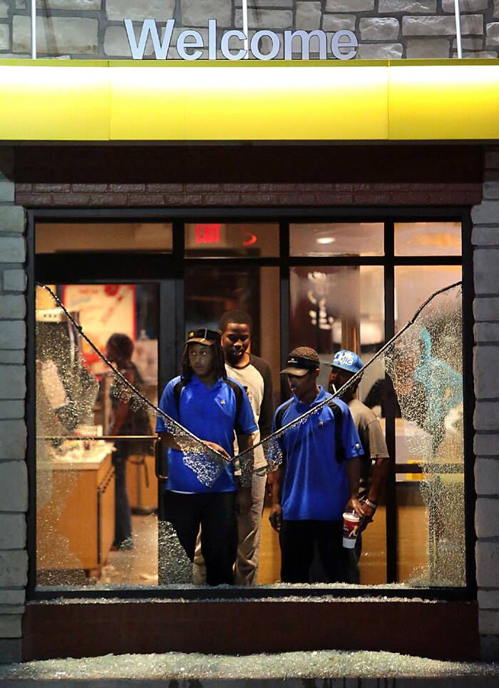 Employees of a McDonald's restaurant watch through a shattered window as riot police move in on protestors in Ferguson, Mo. (Source: AP)