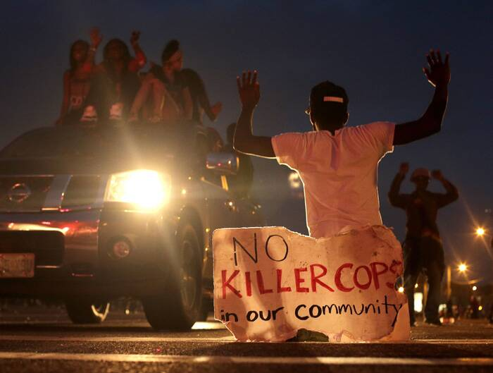 Police advance after tear gas was used to disperse a crowd on Sunday during a protest for Michael Brown, who was killed by a police officer last Saturday in Ferguson, Mo. (Source: AP)