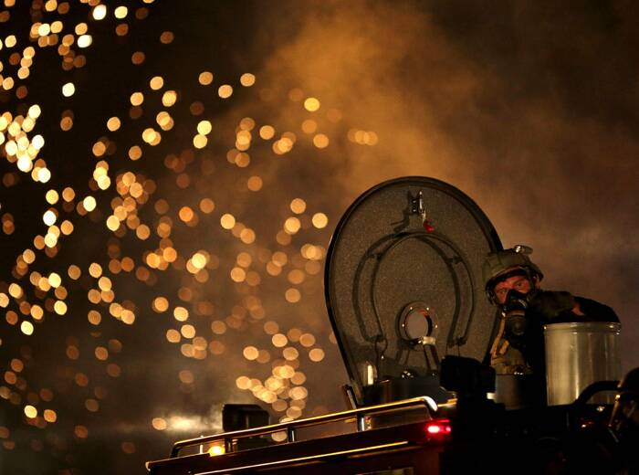 A law enforcement officer on a tactical vehicle watches after a device was fired to disperse a crowd. (Source: AP)