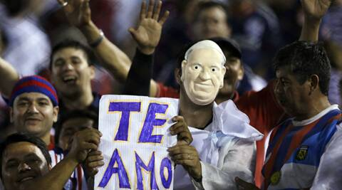 "An Argentina's San Lorenzo fan wearing a Pope Francis mask holds a poster which reads in Spanish ""I love you"" (Source: AP)"