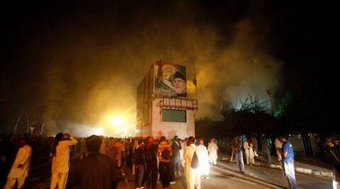 Pakistani protesters gather around a container with portrait of Pakistan's anti-government cleric Tahir-ul-Qadri as police fire tear gas shell to disperse them during clashes in Islamabad. ( Source: AP )