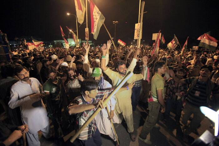 Thousands of supporters of anti-government cleric Tahir-ul-Qadri dance during a march in front of parliament building in Islamabad. (Source: AP)