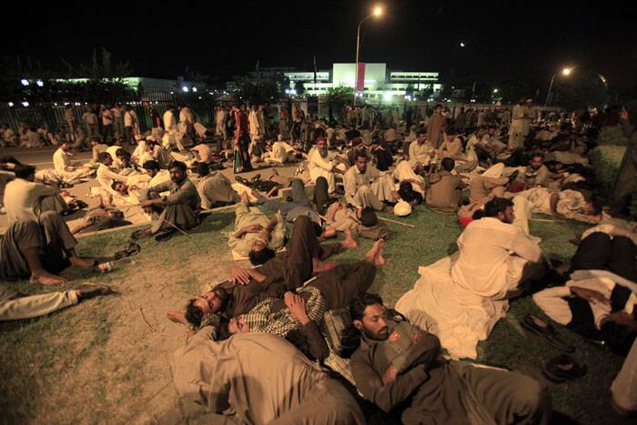 Supporters of Pakistani religious cleric Tahir-ul-Qadri rest in front of the parliament building during a massive rally in Islamabad. (Source: AP)