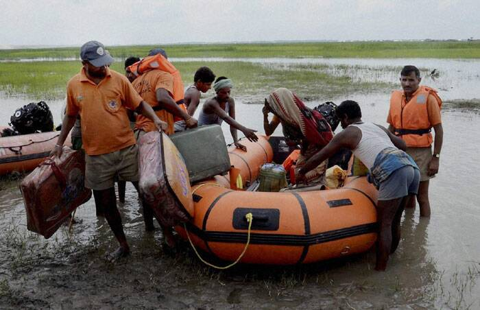 NDRF jawans rescue flood affected villagers near the Indo- Nepal border at Birpur due to danger to Kosi's embankments after heavy inflow of water into the river from Nepal's side in Supaul district of Bihar on Sunday. (Source: PTI)