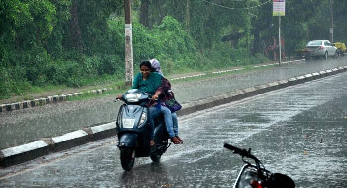 Girls riding a scooter in heavy rains in Patiala on Saturday. (Source: PTI)