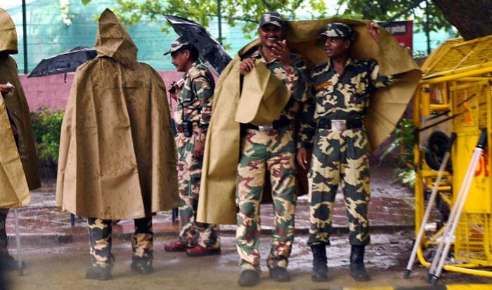 Security personnel use rain coats as it rains in New Delhi on Saturday. (Source: PTI)
