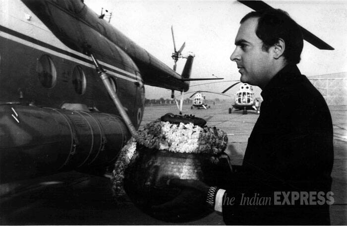 Rajiv Gandhi is seen carrying the flower-bedecked urns that contains the ashes of Indira Gandhi. It was taken to Hindon from Delhi airport on November 11, 1984. (Express archive photo)
