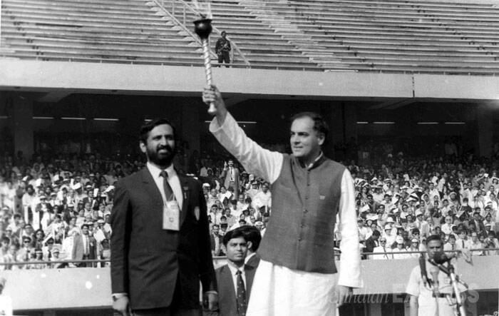 Rajiv Gandhi holding aloft the torch during the inaugural ceremony of Asian Games. Suresh Kalmadi is also seen in this picture. (Express archive photo)