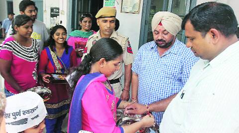 AAP workers tie raakhis  to cops at a police station in Ludhiana on Sunday.  Source: 	Gurmeet Singh