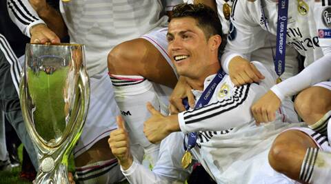 Real Madrid's Cristiano Ronaldo reacts as he poses with the trophy after winning the UEFA Super Cup final against Sevilla (Source: Reuters)