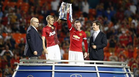 Manchester United forward Wayne Rooney (right) holds the championship trophy with midfielder Darren Fletcher (left) (Source: USA Today Sports)