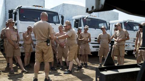 Drivers listen to instructions as they stand near their white trucks with humanitarian aid after parking in a field about 28 kilometers from Ukrainian border in Rostov-on-Don region, Russia, Thursday, Aug. 14, 2014. (Source: AP)