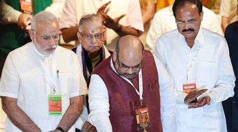 BJP President Amit Shah lights the lamp as Prime Minister Narendra Modi and senior leaders M M Joshi and M Venkaiah Naidu look on during the party's National Council meet in New Delhi on Saturday. Source: PTI Photo