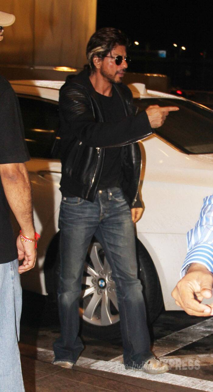 Shah Rukh Khan, who has been busy with the post production work of 'Happy New Year', wore a black leather jacket with denims and his famous blonde streak at the airport as he arrived with his eldest son Aryan. (Source: Varinder Chawla)