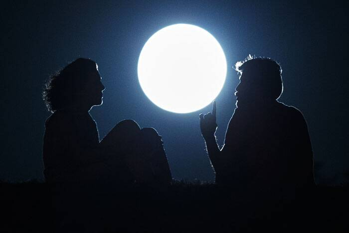 A couple talk as they sit against  the perigee moon, also known as a supermoon, in Madrid. The phenomenon, which scientists call a 'perigee moon', occurs when the moon is near the horizon and appears larger and brighter than other full moons. (Source: AP)