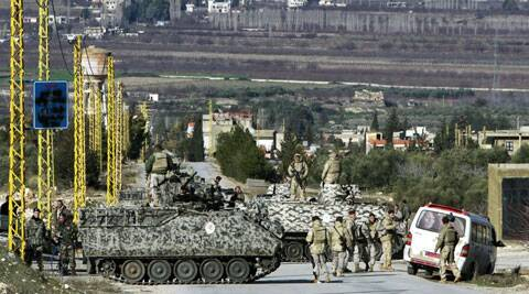 In this Saturday, Feb. 2, 2013 file photo, Lebanese army soldiers search civilians at a checkpoint at the entrance of Arsal, a Sunni Muslim town near the Syrian border in eastern Lebanon. (Source: AP)