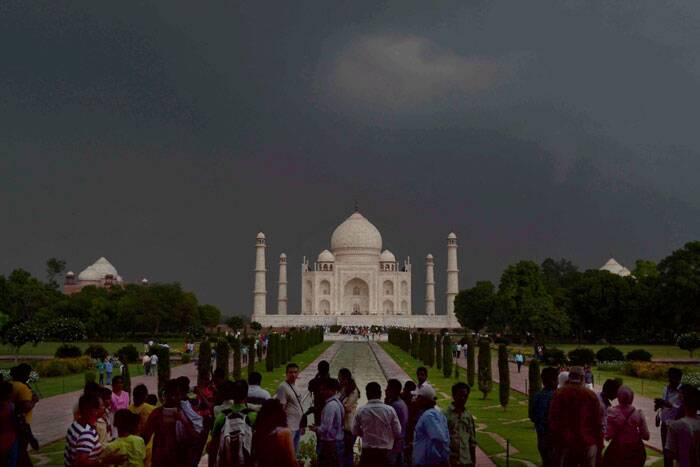 Visitors are seen enjoying the cloudy weather at the Taj Mahal in Agra on Thursday. (Source: PTI)