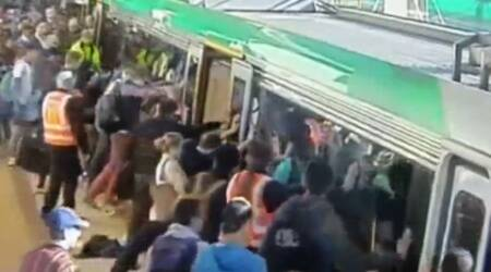 The footage showed dozens of people rushing to help tilt the carriages to free the man.