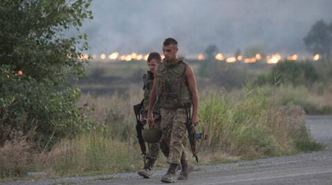 Ukrainian government soldiers walk past a burning field after shelling their base by pro-Russian rebels artillery near Illovaisk, Donetsk, Ukraine. (Source: PTI)