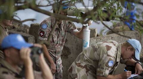 U.N. peacekeepers from the United Nations Disengagement Observer Force, also known as UNDOF, observe Syria's Quneitra province at an observation point on Mt. Bental in the Israeli-controlled Golan Heights, overlooking the border with Syria, Friday, Aug. 29, 2014. (Source: AP)