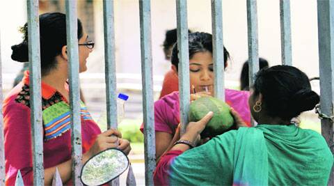 A Civil Services aspirant sips coconut water at an examination centre in New Delhi on Sunday. (Photo: Ravi Kanojia)