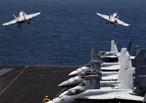 US F/A-18 fighter jets take off for mission in Iraq from the flight deck of the US Navy aircraft carrier USS George H W Bush, in the Persian Gulf. (Source: AP)