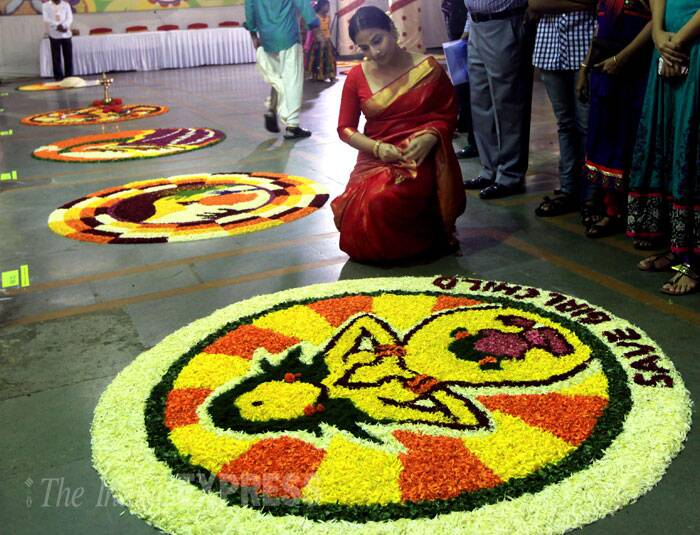 Vidya Balan, who was dressed in her favourite red Kanjeevaram sari complete with a gajra, takes a look at the flower rangoli. (Source: Express Photo by Ganesh Shirsekar)