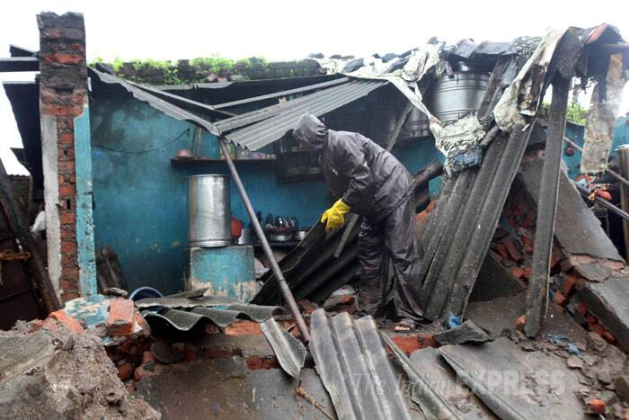 The incident took place in Nagpure compound around 5 AM when the wall of a hut came crashing down due to heavy rains. (Source: Express photo by  Deepak Joshi)
