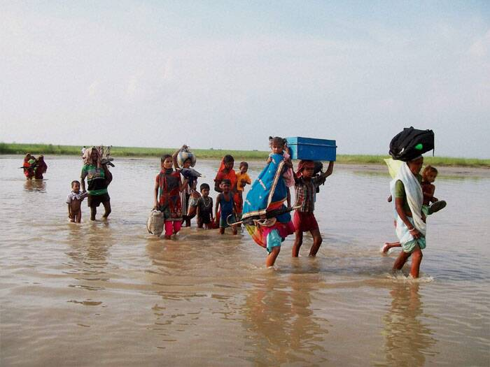 Villagers moving to safer places due to the danger to Kosi's embankments after heavy flow of water into the river from Nepal's side in Supaul, Bihar on Sunday. (Source: PTI)