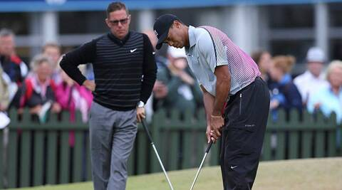 Tiger Woods is watched by his coach Sean Foley during the