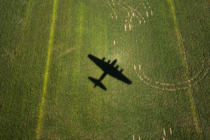 "Aerial Images photographed of the Burning Man Caravansary, the  Second World War B17 Bomber and the on-land portrait of the  Founding Father of Turkey Mustafa Kemal Atartuk is worth inclusion into the Indian Express Top Frames. <br /> The World War II B-17 bomber, ""Sentimental Journey,"" casts a shadow as it flies over fields outside of Culpeper, Va. on August 26, 2014. The plane will be available for cockpit tours and flights at Culpeper Regional Airport. (Source: AP)"