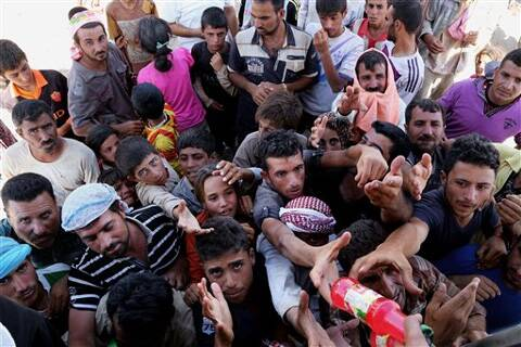Displaced Iraqis from the Yazidi community gather for humanitarian aid at the Iraq-Syria border at Feeshkhabour border point. Source: Ap photo