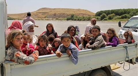 In this Sunday, Aug. 10, 2014, displaced Iraqis from the Yazidi community cross the Iraq-Syria border at Feeshkhabour bridge over Tigris River at Feeshkhabour border point, northern Iraq.  Source: AP phot