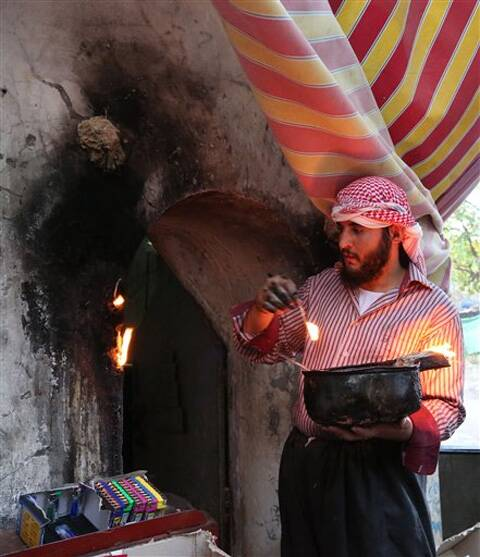 An Iraqi Yazidi man lights candles near the holy Lalish temple in the Mountains of Shikhan near Dahuk. Source: AP photo
