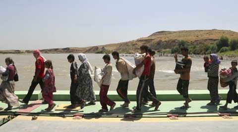 Displaced Iraqis from the Yazidi community cross the Syria-Iraq border at Feeshkhabour bridge over Tigris River at Feeshkhabour border point, northern Iraq. (Source: AP)