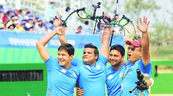 (From left) Abhishek Verma, Rajat Chauhan and Sandeep Kumar celebrate with their coach after winning the compound men's team gold medal on Saturday. Source:AP