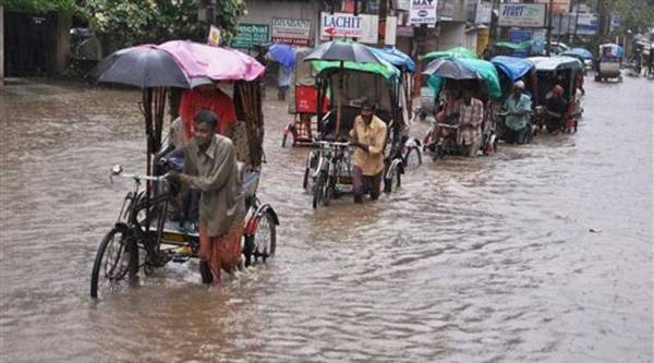 Rickshaw puller wades through a flooded street after heavy shower, in Guwahati on Monday. (Source: PTI)