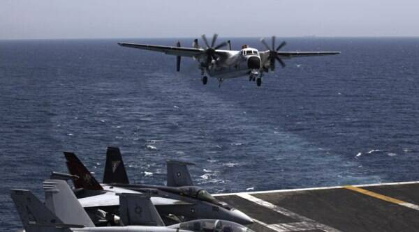 FILE - In this Monday, Aug. 11, 2014 file photo, a U.S. military plane lands on the U.S. Navy aircraft carrier USS George H.W. Bush, in the Persian Gulf. (Source: AP)