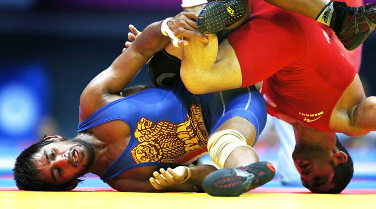 Iran's Masoud Esmaeilpoorjouybari (Red) fights India's Bajrang in their Men's Freestyle 61 kg gold medal wrestling match. (Source: Reuters)